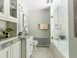 Hall bathroom with granite countertops and glass enclosed tub