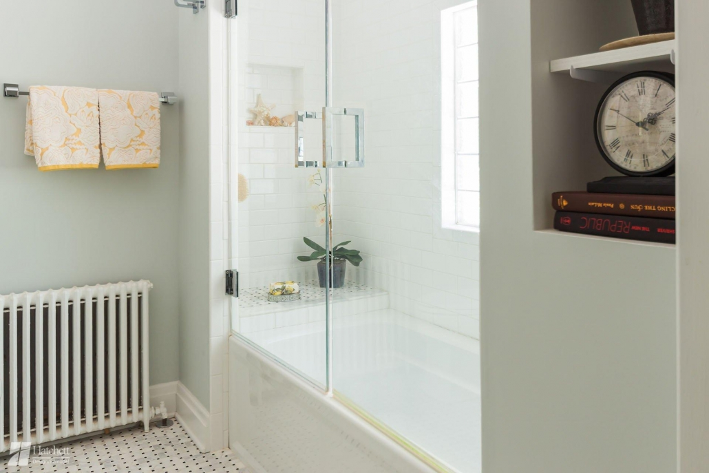 Shower and tub combo with subway tile walls and a bench.