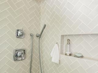 Shower wall subway tiles in herringbone pattern